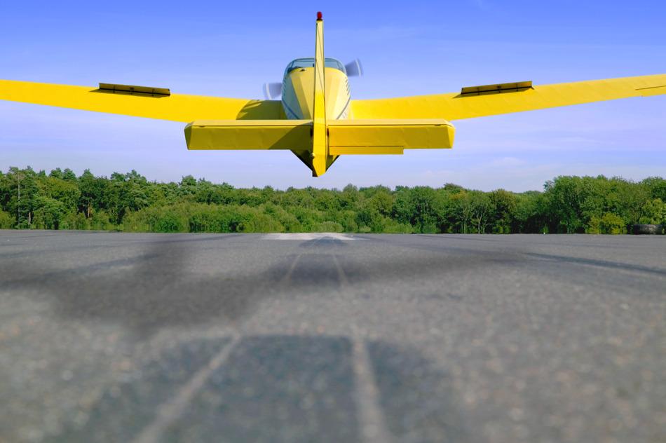 Light aircraft landing on a tarmac runway.